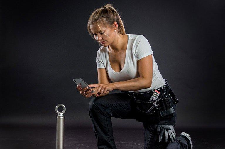 Mitarbeiterin dokumentiert einen Anschlagpunkt mit der Lock Book Docu App auf dem Handy